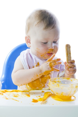A young blue-eyed child feeding pumpkin puree in a chair for feeding photo