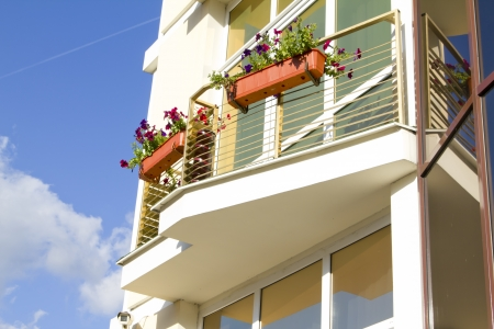 balcony with petunia flowers on modern apartments building Foto de archivo