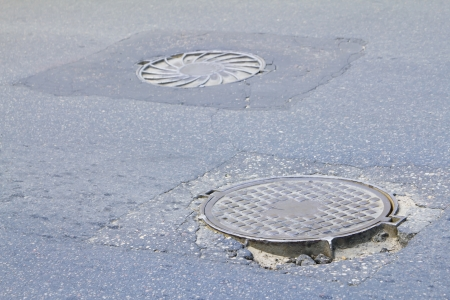 two iron manhole covers on the road photo