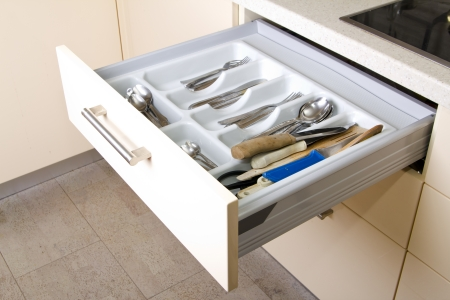 Open Organized Kitchen Drawer with utensils Stock Photo