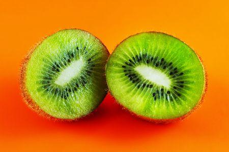 hairy pear: sliced open kiwi macro shot on a orange background
