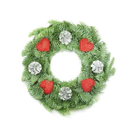 christmas wreath with berries and other ornaments made from real pine boughs isolated on white background