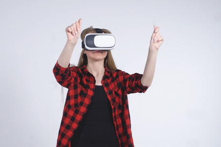 The Young Girl in the Virtual Reality Helmet is Actively Playing the Game Stok Fotoğraf