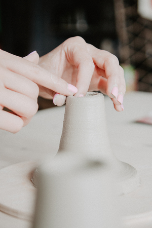 Creating a jar or vase of white clay close-up. Woman hands making clay jug.