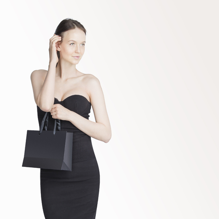 Close-up of beautiful girl wearing black dress holding shopping bags isolated on white background with copyspace