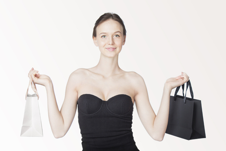 Close-up of beautiful girl wearing black dress holding shopping bags isolated on white background