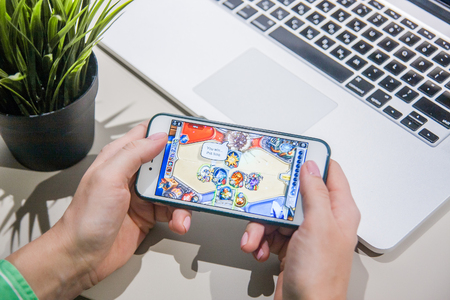 Los Angeles, California, USA - 25 February 2019: Hands holding a smartphone with Hearthstone game on display screen