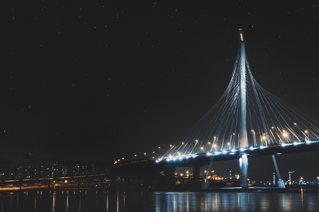 Beautiful cable-stayed bridge in St. Petersburg, Russia, with starry sky and city lights Stock Photo