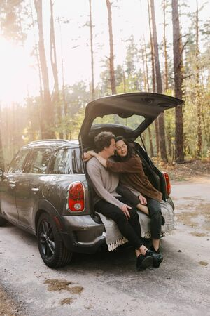 Young beautiful couple relaxing together sitting on a car trunk