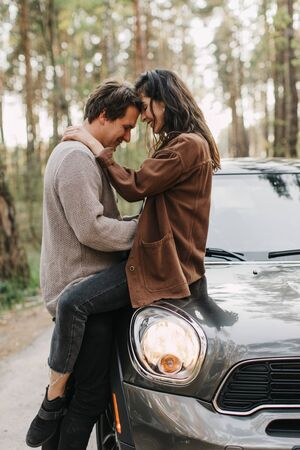 beautiful young couple in love kisses and hugs sitting on a car