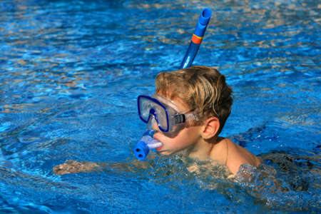skindiver: The boy with a tube and a mask of the skin-diver floats in pool