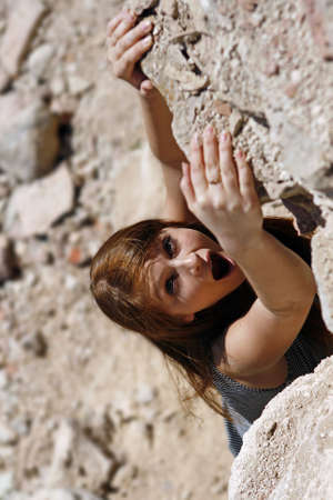 hangs: The girl hangs on the brink of a rock and asks about the help Stock Photo