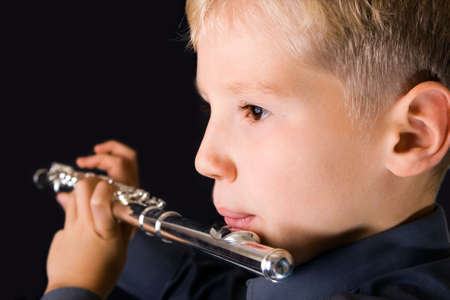 The ten years boy playing a flute photo