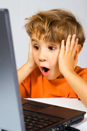 sensational: The kid has opened a mouth from surprise, looking at the laptop screen 스톡 사진
