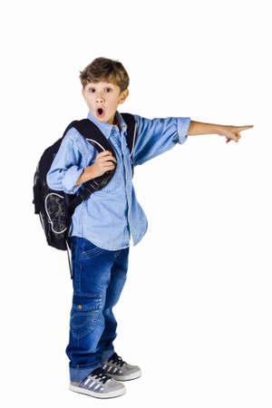 asombro: El escolar de 6 años de edad, con ropa de jeans, con asombro señala con el dedo a un lado Foto de archivo