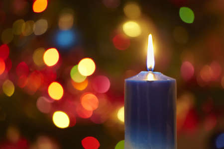 candlelight: Christmas candle against shone bulbs of a New Year Stock Photo