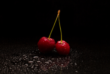 Two cherries in drops of water on a black background Standard-Bild