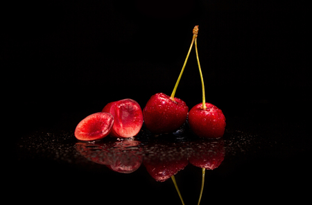 Cherry in drops of water on a black background