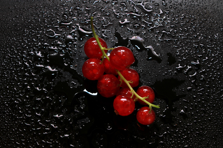 Red currant, lying on a black background in droplets of water