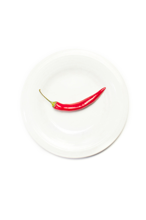 Red hot chilli pepper on round plate isolated on white background top view closeup Standard-Bild - 104506675