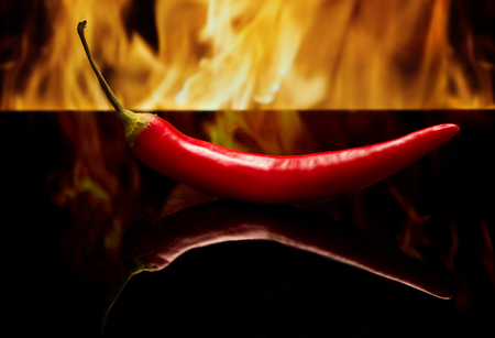 Red pepper on a black background in the fire. Side view