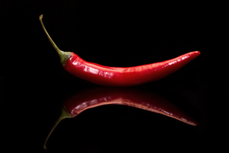 Red pepper on a black background. Side view