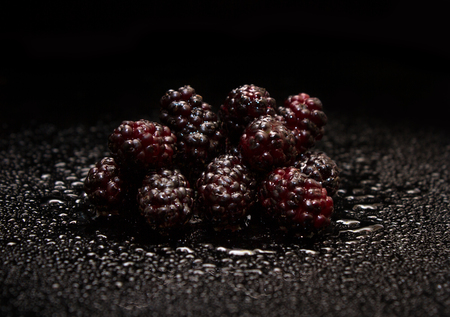 Black background of fresh mulberry.
