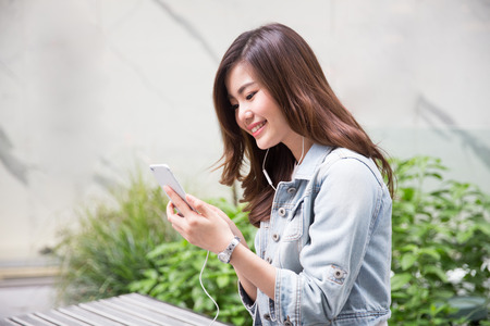 Young asian girl playing mobile phone