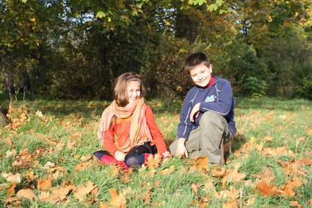 ten year old: Two children collecting autumn leaves Stock Photo