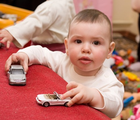 Baby indoors playing with toy truck photo