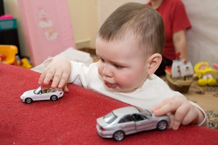 twenty four month old: Baby indoors playing with toy truck Stock Photo