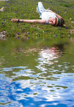 A girl lies on a lawn ashore lake Stock Photo - 4399766