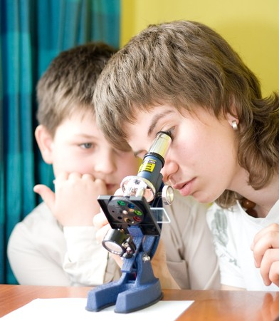 boy and girl with a microscope in a laboratory photo