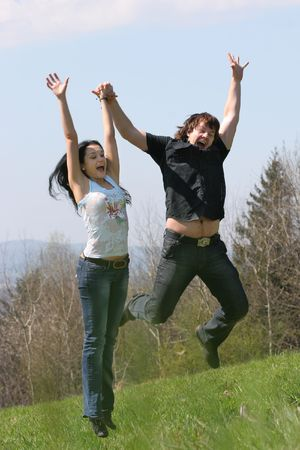 Couple jump on the meadow photo