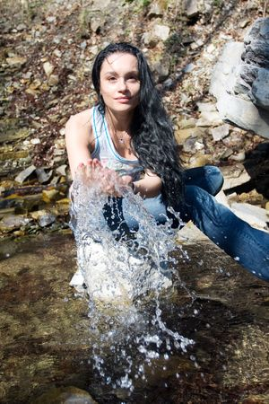 woman plays with water near waterfall photo