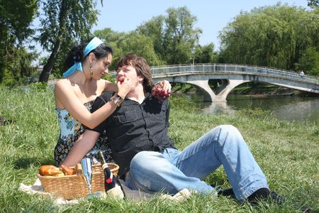 midlife: Couple sitting together by a lake with a picnic basket. Stock Photo