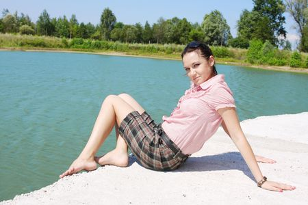 The beautiful girl on the bank of the summer river Stock Photo - 5293443