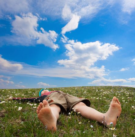 Hiker lies on meadow in mountains