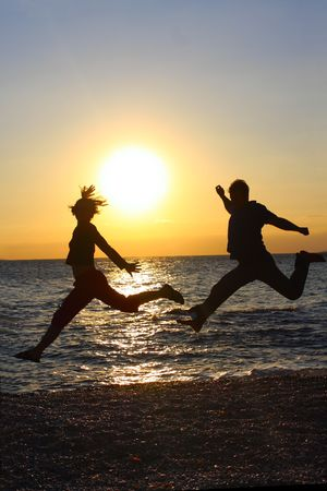 Silhouettes of happy people jumping at sunset  photo