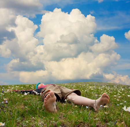 Hiker lies on meadow in mountains  photo