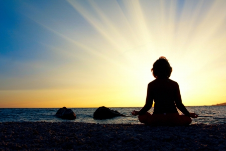 mind set: Silhouette of a woman meditating by the sea Stock Photo