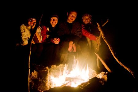 People near campfire in forest Stock Photo