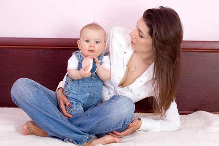 Mutter spielt mit Babygirl auf Bett