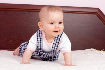 babygirl: Babygirl is playing on bed Stock Photo