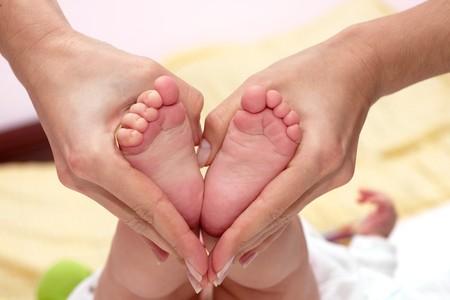 pied jeune fille: B�b� pieds dans les mains du dico.  Banque d'images
