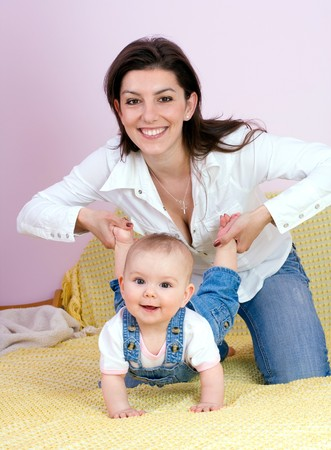 mom holding baby: Mother plays with babygirl on bed