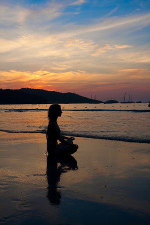 inner beauty: Silhouette of a woman meditating by the sea