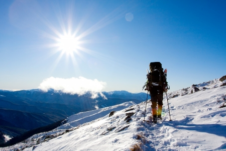 Hiker in winter in mountains photo