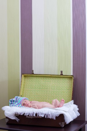 newborn baby sleeps in the suitcase photo