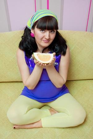 pregnant woman eating fruits at home  photo